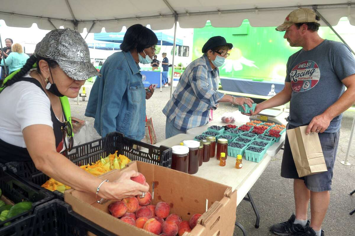 Mike Maskell of Smith Acres, in Niantic, helps, from left, Milda Rodrigues, Marie Young and Carmen DeLeon as they shop at East Side Farmers Market, in Bridgeport, Conn. July 14, 2021. Run by the Bridgeport Farmers' Market Collaborative, the east side market is one of seven held around the city every week from now until October.