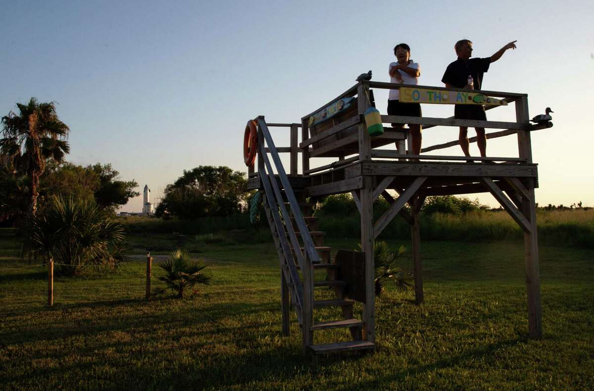 """Sarah and Rob Avery stand on their observation deck and watch the sun set, as a SpaceX rocket is seen in the background, Tuesday, June 15, 2021, in Boca Chica Village, an unincorporated community near Brownsville. """"Not only are they looking to steal our home, but they're looking to steal our retirement,"""" Rob said of SpaceX. """"We appreciate what they do, but not here."""" The couple described the company's efforts to buy their house and others nearby as it expands its rocket launch facilities and activities in the area. The couple felt the offers they had received from SpaceX were not fair."""