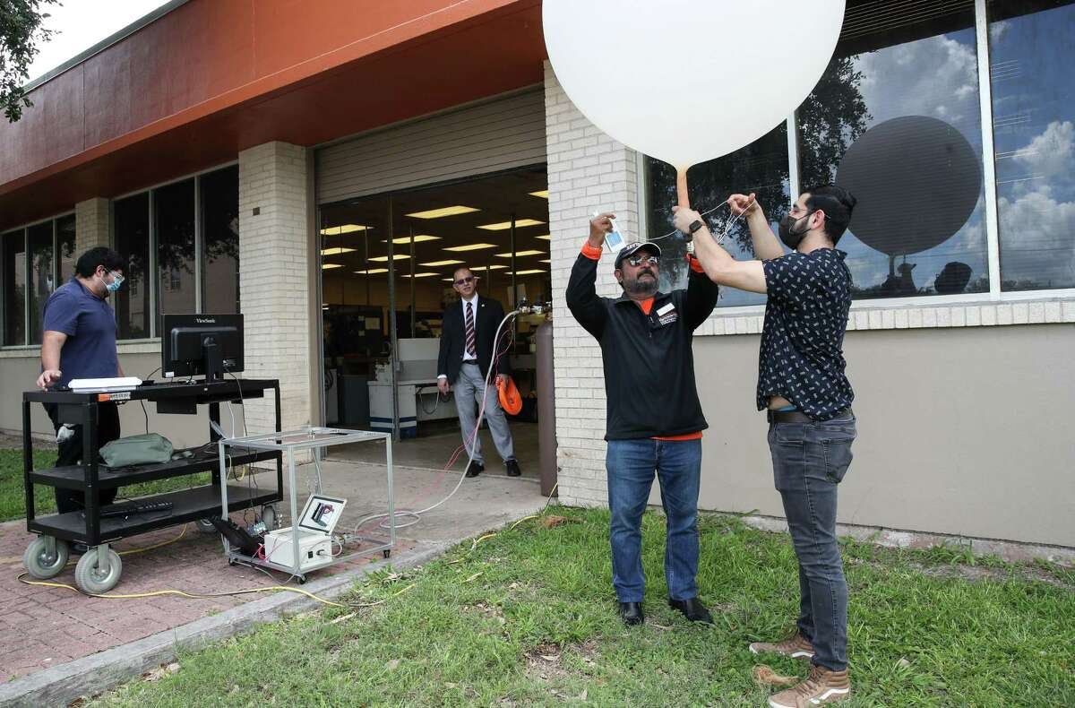 Professor Immanuel Edinbarough, center-right, and Matthew Ramos, a student who just graduated, demonstrate an automated weather balloon launching device Wednesday, June 16, 2021, at the University of Texas Rio Grande Valley in Brownsville.