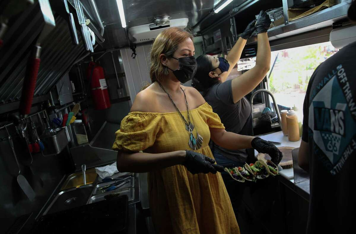 Mayra Garcia Guzman works on her family's BeachPaws food truck with her husband and son Thursday, June 17, 2021, in South Padre Island.