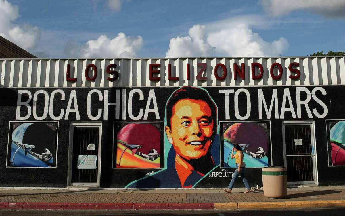 """A woman walks by a mural featuring SpaceX founder Elon Musk that is promoting an art exhibit titled """"Boca Chica to Mars,"""" on Wednesday, June 16, 2021, in Brownsville. SpaceX has been building launch facilities in Boca Chica, an unincorporated area near the city."""