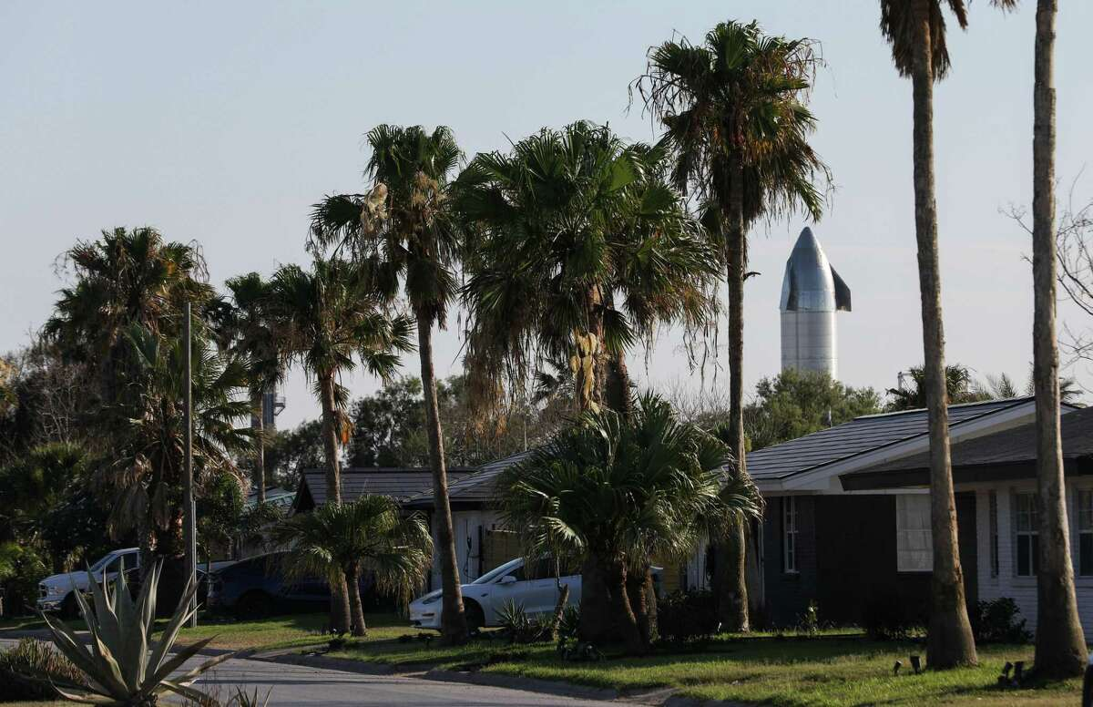 A SpaceX rocket sits behind homes Tuesday, June 15, 2021, in Boca Chica Village, an unincorporated area near Brownsville.
