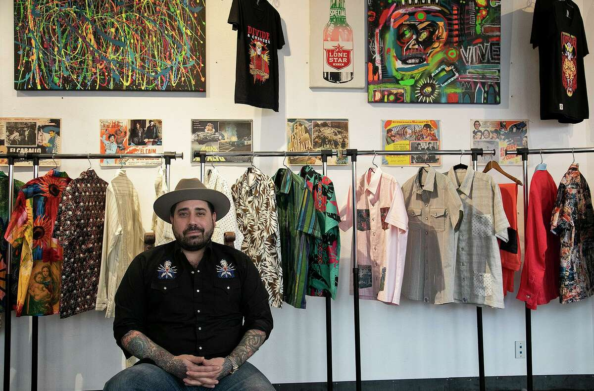 Javier Trevino, owner of Divide & Conquer Denim & Leather, sits next to a row of his custom guayaberas at his store in downtown San Antonio on July 9, 2021.