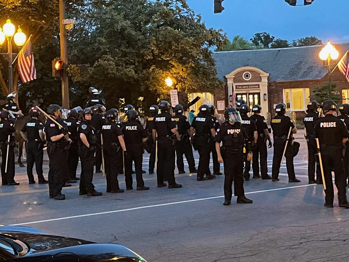 Police in riot gear line up in Saratoga Springs on Wednesday as civil rights protesters demonstrated downtown. Police later descended on the demonstrators, arresting five men.