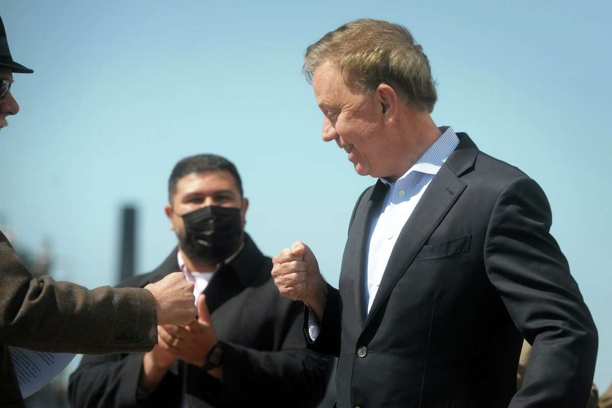 Gov. Ned Lamont is greeted as he steps up to speaks at a news conference on the Bridgeport Boatworks property, in Bridgeport, Conn., on April 5, 2021. The project is expected to create about 100 jobs.