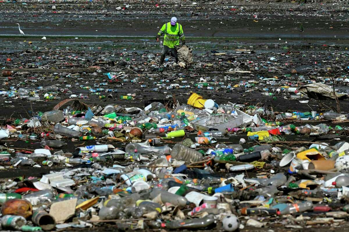 A man collects garbage, including plastic waste, at the beach of Costa del Este, in Panama City, on April 19, 2021. (Luis Acosta/AFP/Getty Images/TNS)