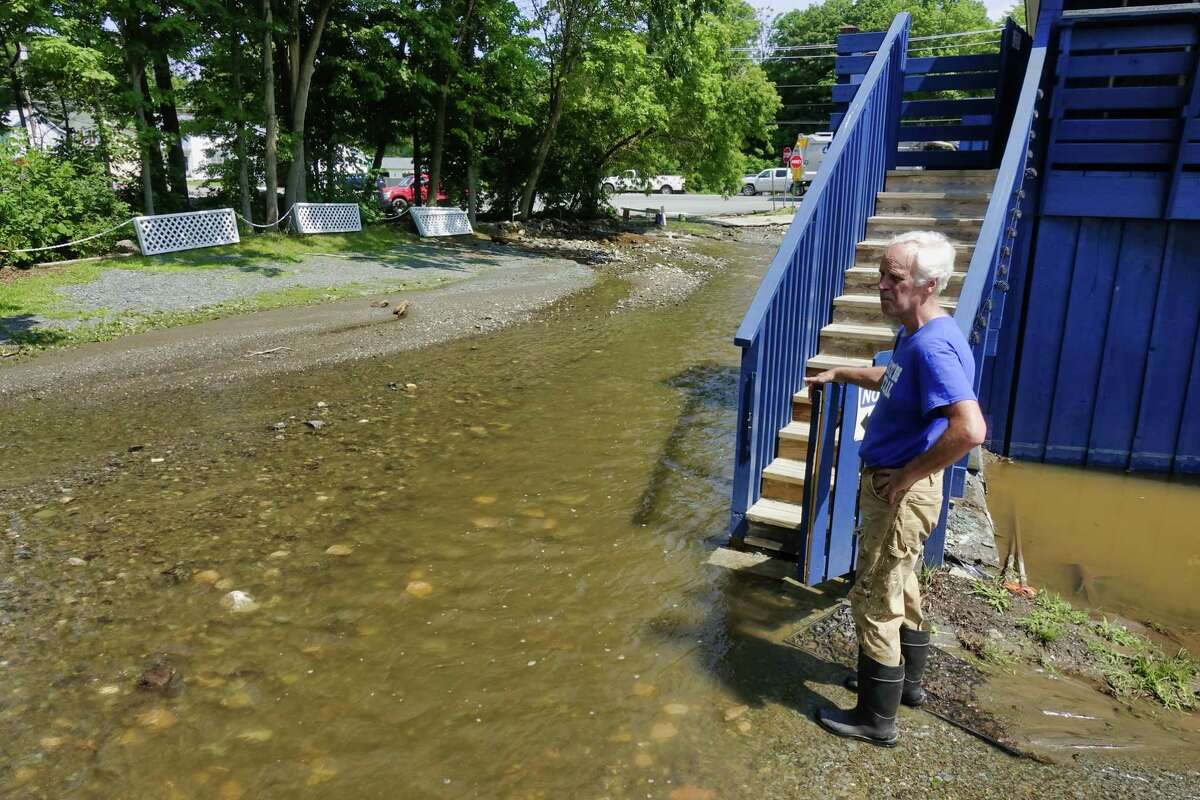 """Kevin Tighe, owner of Tighe's Bistro Americain, stands in the parking lot of his restaurant, which now has a river running through it, on Thursday, July 15, 2021, in Averill Park, N.Y. Heavy rains Wednesday afternoon caused flooding in the bistro's basement and washed a large amount of debris into the parking lot. Tighe and his wife had their home flooded Wednesday and some of their rental properties were also damaged. """"The restaurant will come second, first we need to make sure our renter's homes are livable for them"""", Tighe said. (Paul Buckowski/Times Union)"""