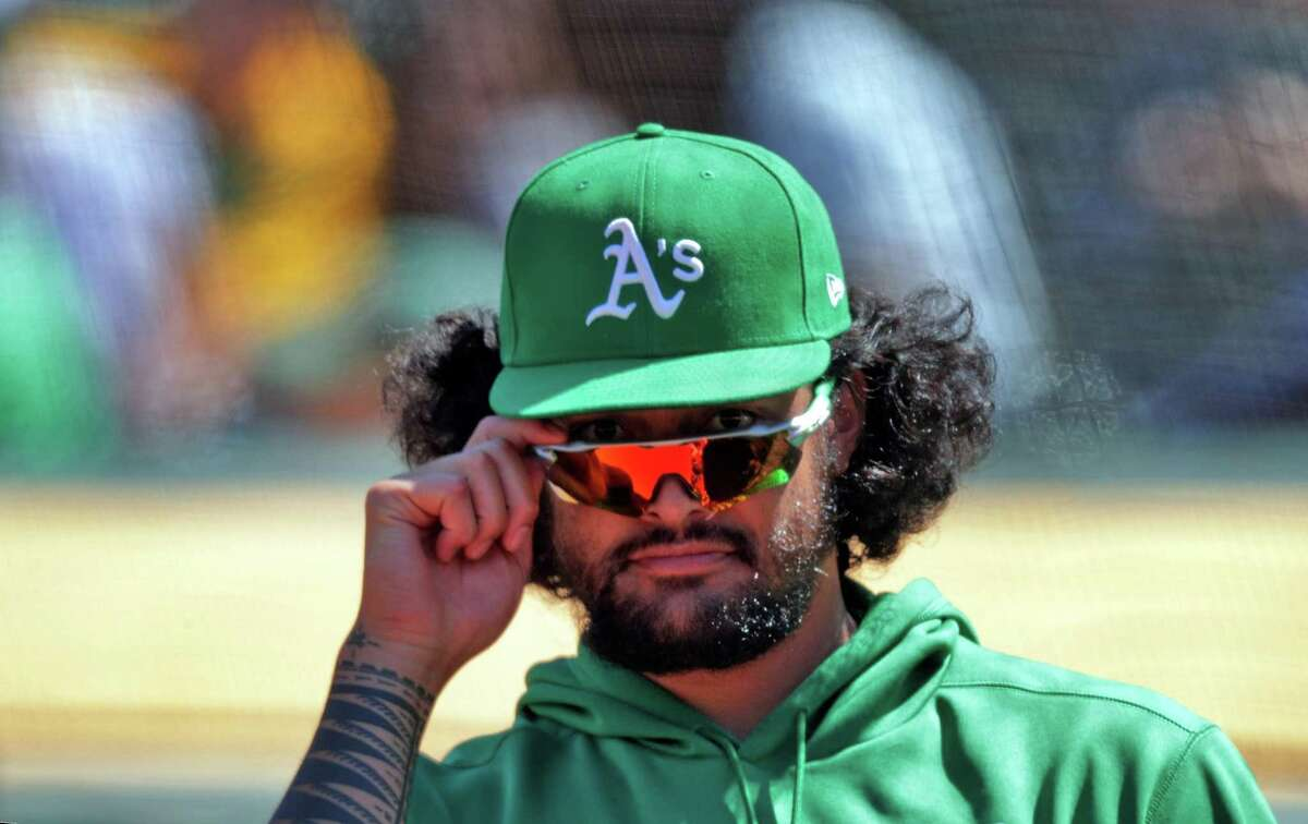 A's pitcher Sean Manaea (55) takes a peak at the fans over his glasses while in the dugout during the game as the Oakland Athletics played the Los Angeles Angels at the Coliseum in Oakland, Calif., on Sunday, May 30, 2021.