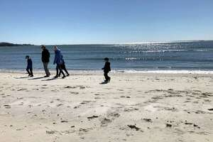 A family strolls the beach at Rocky Neck State Park in East Lyme.
