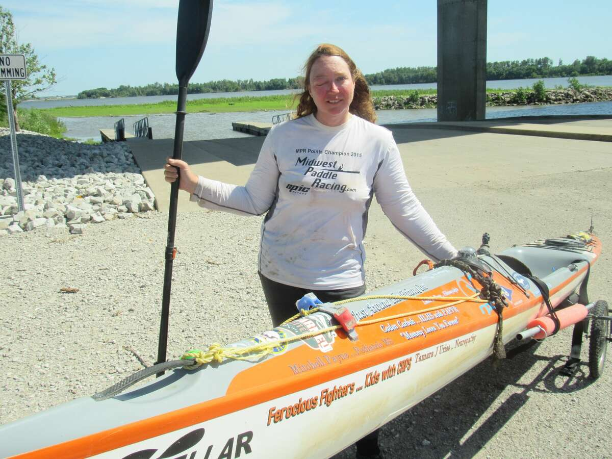 Competitive kayaker Traci Lynn Martin, of Kansas City, Missouri, stands beside her kayak on June 14 in Alton. This week she set the world record for the fastest time for a solo female kayaker to travel the Mississippi River: 55 days, eight hours and seven minutes.