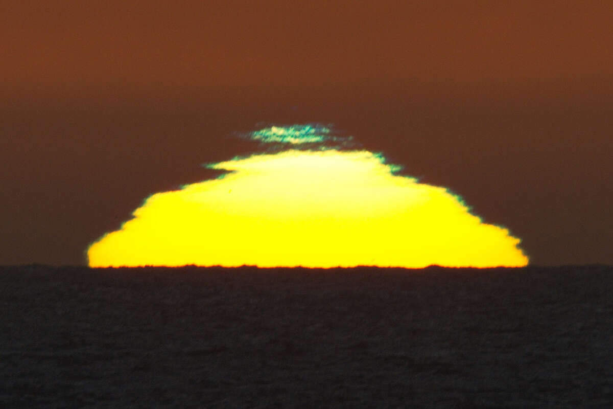 A photographer captures the green flash at sunset at Poplar Beach in Half Moon Bay.
