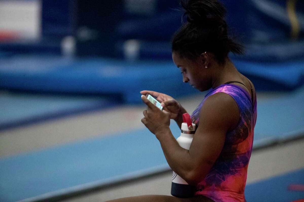 Olympic gymnast Simone Biles watches video of her floor exercise between reps during a workout as she prepares for the upcoming Tokyo Olympics at World Champions Centre Tuesday, July 6, 2021 in Spring.