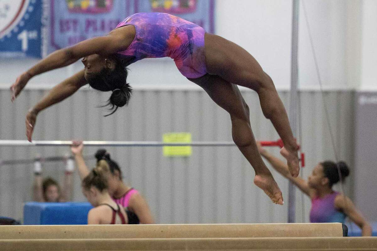 Olympic gymnast Simone Biles, working out at her home gym in early July, will compete in the balance beam in Tokyo on Tuesday.