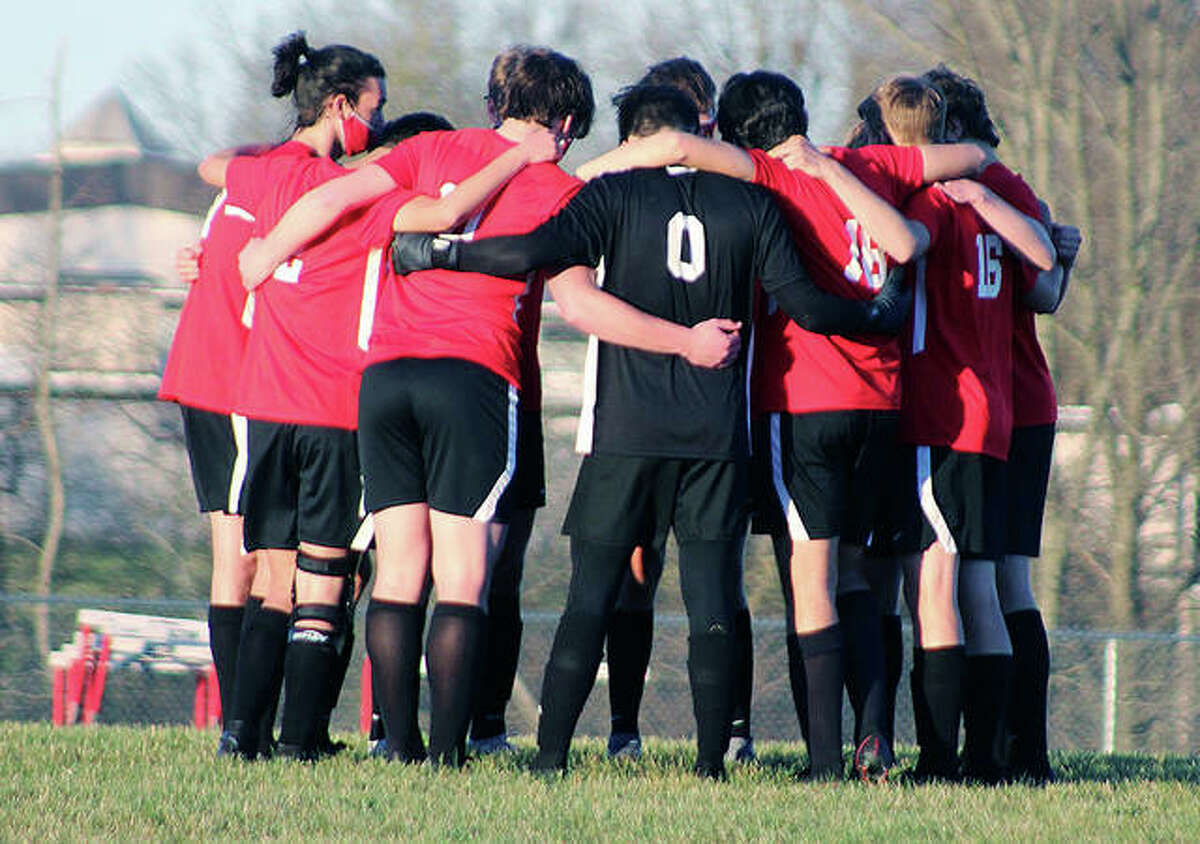 Members of the Alton High boys soccer team huddle prior to the start of a game last spring against O'Fallon at AHS.