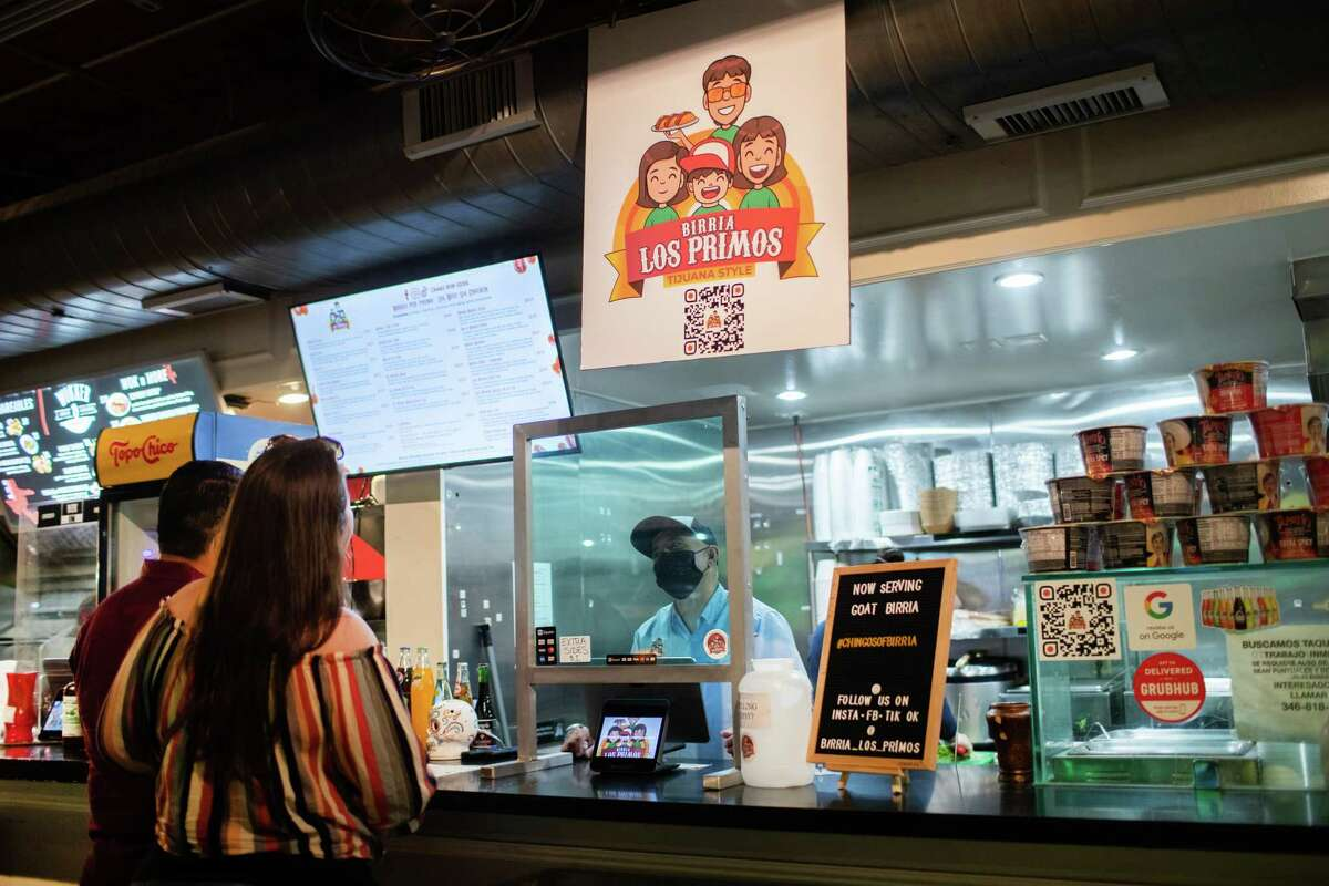 Birria Los Primos owner Oscar Garcia takes an other from his clients, Thursday, July 15, 2021, in Houston. The management of the restaurant says Uber Eats has ripped them off to the tune of $20K.