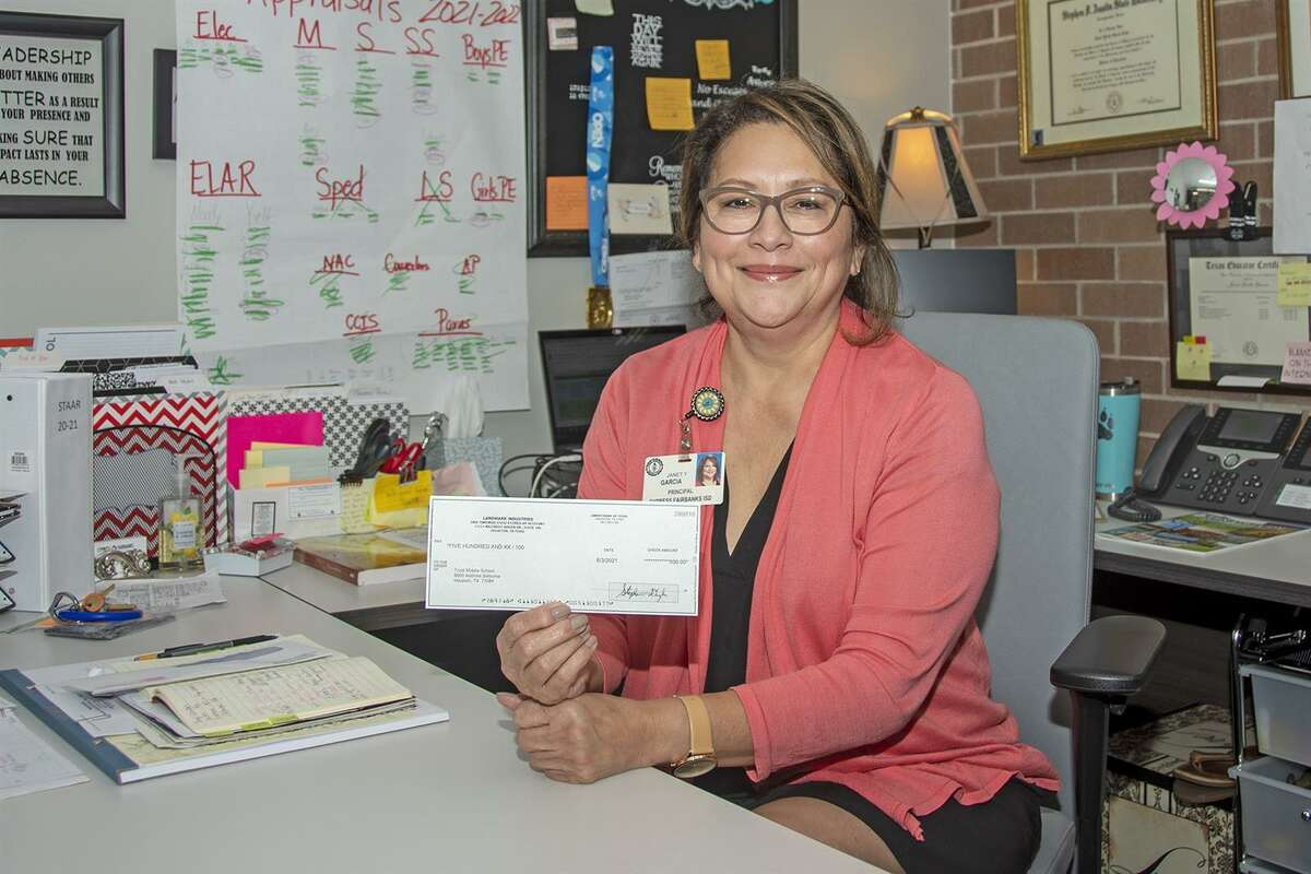 Truitt Middle School Principal Yvette Garcia holds a $500 check donated to the campus from CFISD community partner Landmark Industries/Timewise Food Stores. The funds will be used to fund a new robotics club.