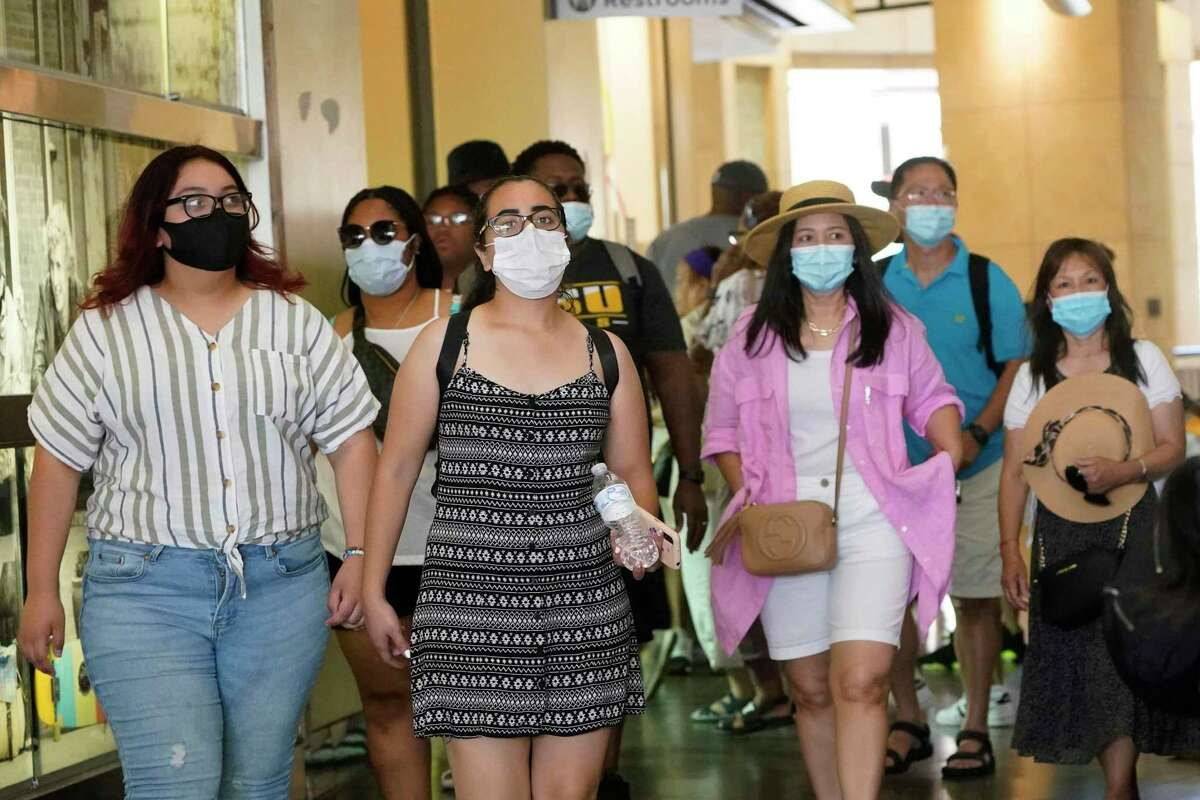People wear masks as they walk in a shopping district in the Hollywood section of Los Angeles. With cases rising, LA County has reinstated its mask mandate.