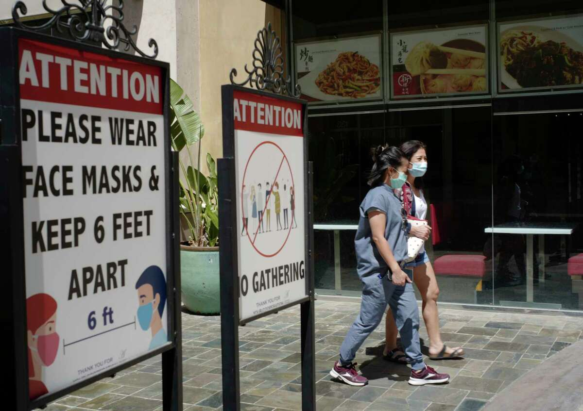 File - In this June 11, 2021 file photo customers wear face masks in an outdoor mall with closed business amid the COVID-19 pandemic in Los Angeles.