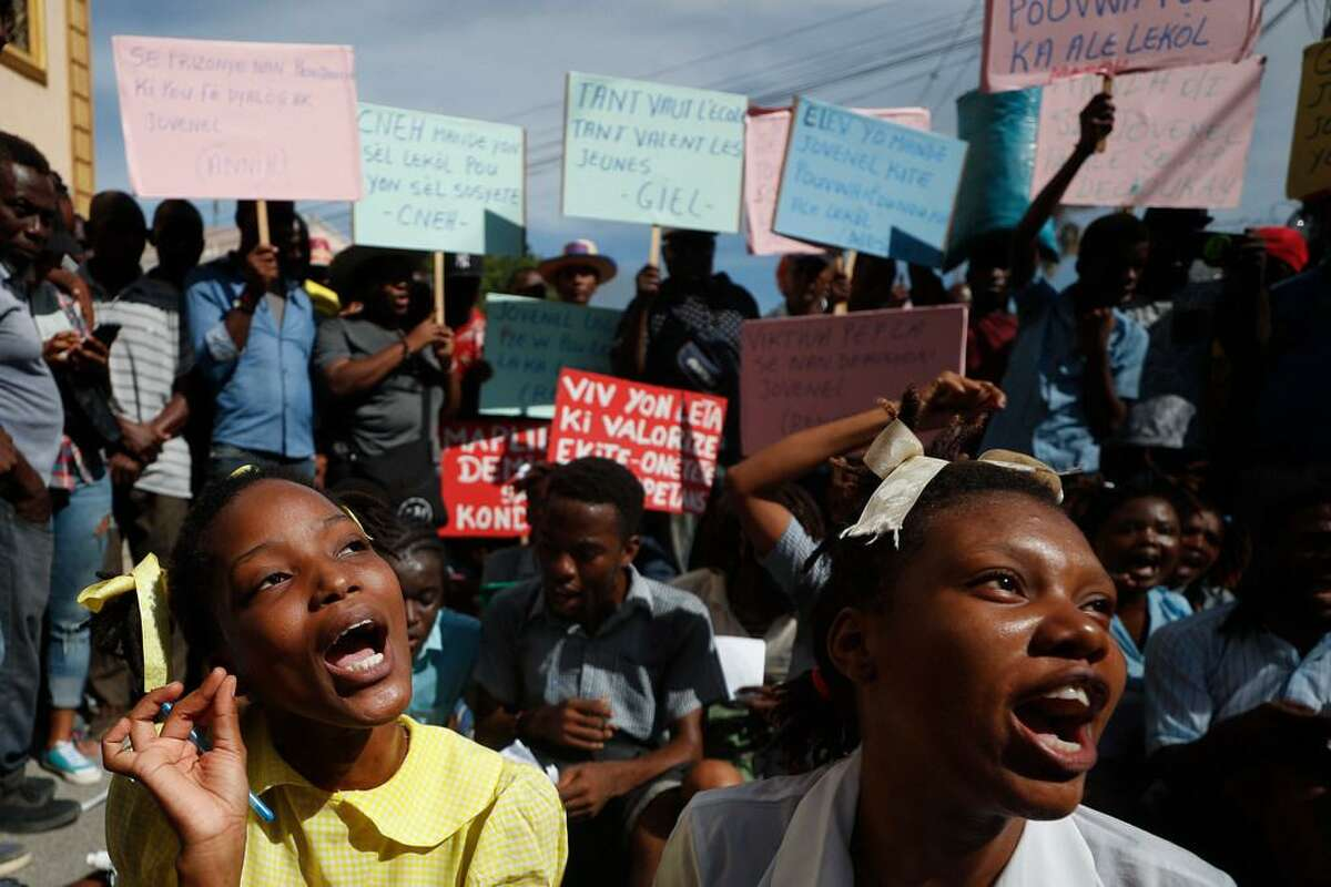 A theater troupe of university students perform as grade school students reciting a lesson on Haiti's constitution and government, during a protest calling for President Jovenel Moïse to resign so that schools can reopen, in Port-au-Prince, Haiti, Monday, Oct. 21, 2019. Many schools around the country have now been closed for more than a month as protests block roads and paralyze the economy.