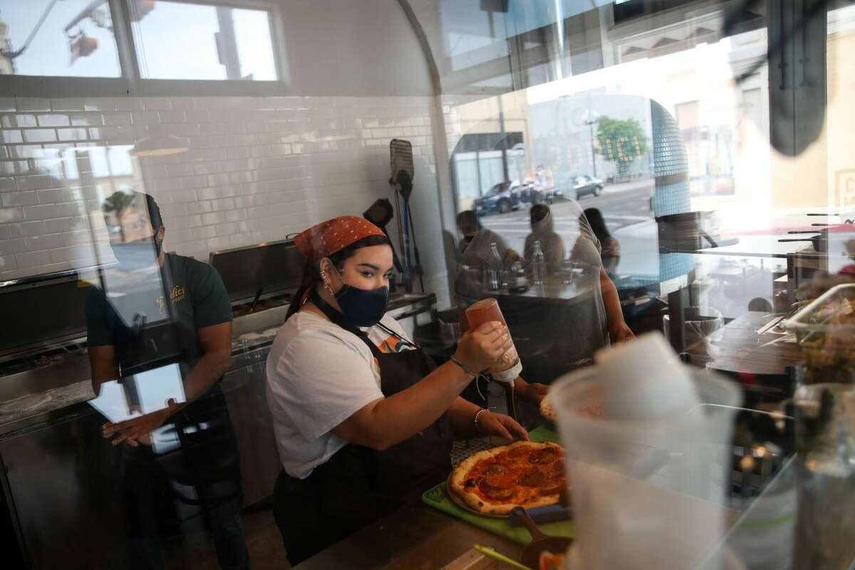 Analize Velazquez prepares a pizza as she works expo Thursday, June 17, 2021, at Dodici Pizza & Wine in Brownsville. Parts of downtown Brownsville are targeted for revitalization efforts as SpaceX builds launch facilities nearby.