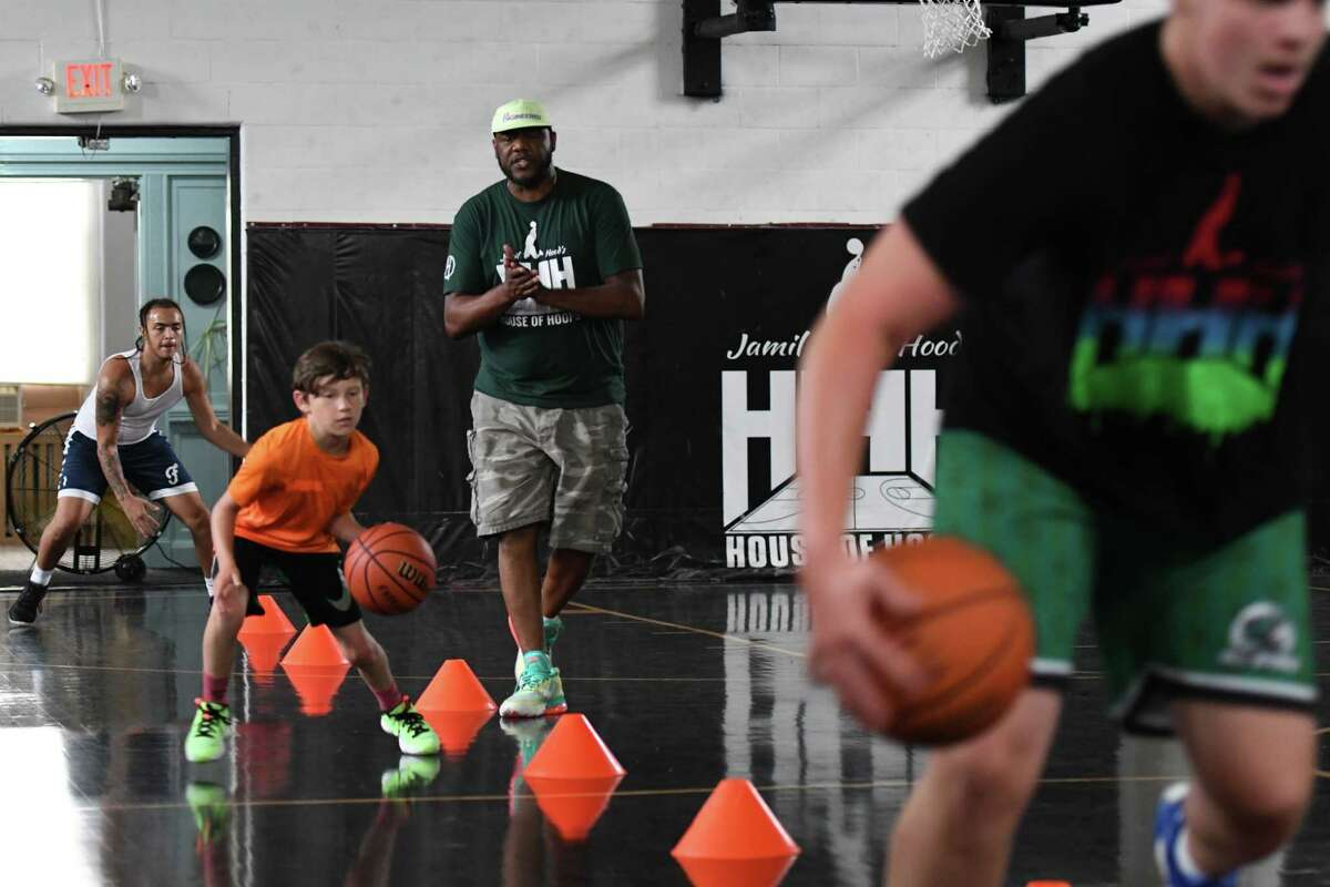 Jamil Hood works with children on their basketball skills during a Hoods' House of Hoops basketball camp on Thursday, July 1, 2021, at his facility on First Street in Albany, N.Y. (Will Waldron/Times Union)