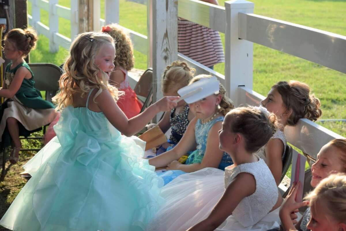 A 2021 Little Miss Jersey County Fair entrant keeps a fellow contestant cool in the 90-degree temperatures during the Wednesday pageant in Jerseyville.
