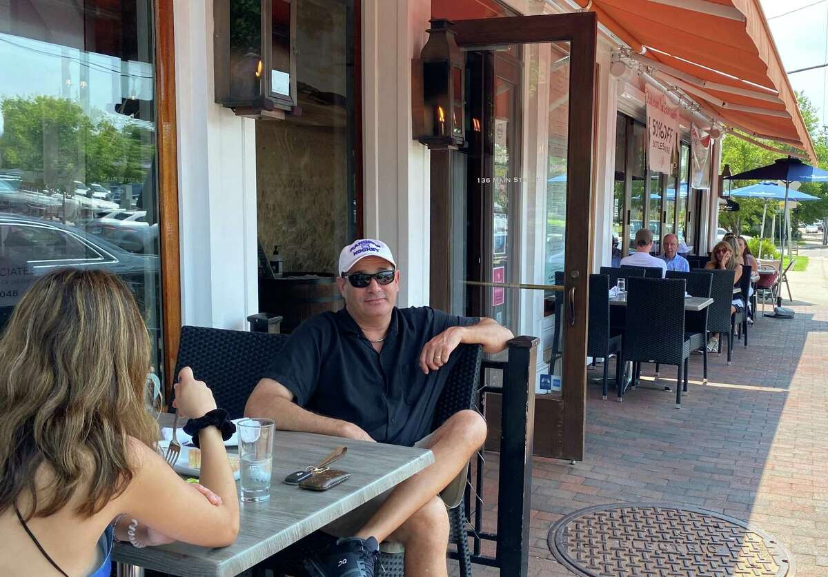 People sat outside in front of New Canaan's nearly 40 eateries, near noon on July 15, 2021. Here patrons are enjoying Spiga restaurant on Main Street.