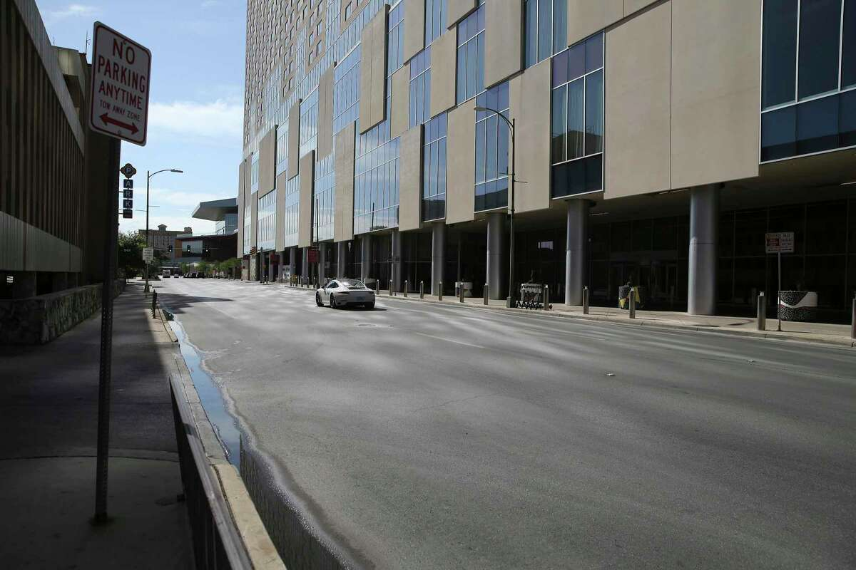 A lone vehicle zips down Houston Street near the Grand Hyatt near the Henry B. Gonzalez Convention Center on May 14, 2020. From the early days of the COVID-19 pandemic, convention cancellations began piling up and hotel reservations were suffering.
