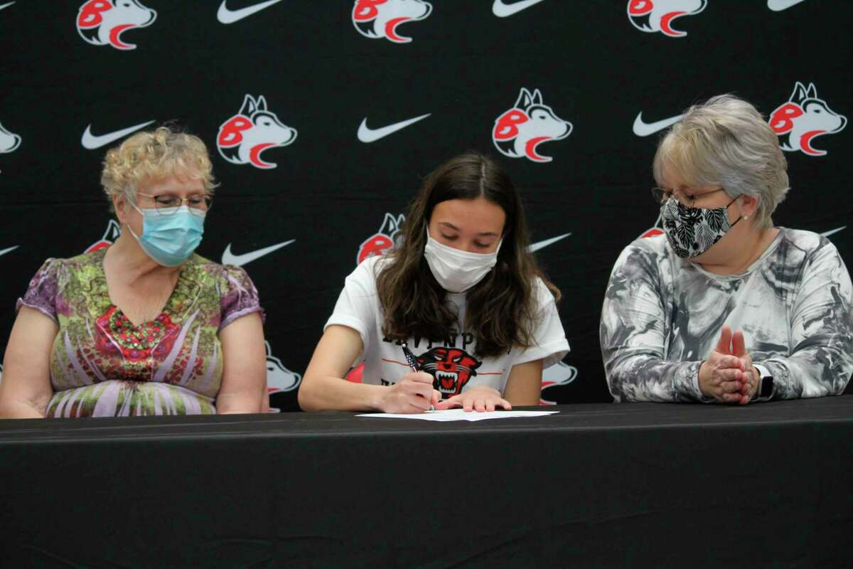 Cierra Guay signs her letter of intent to run for Davenport University during a ceremony in May. (Robert Myers/News Advocate)