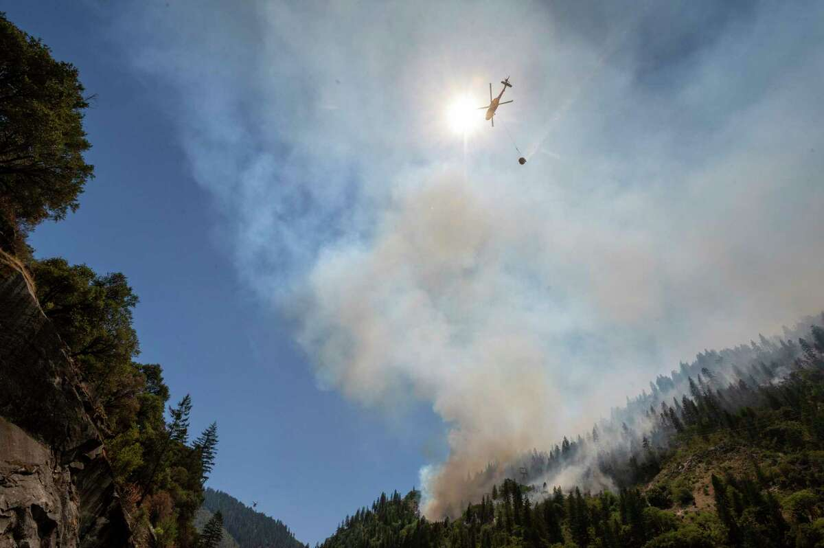 Helicopters drop water to battle the Dixie Fire on Highway 70 in the Feather River Canyon in Plumas County.