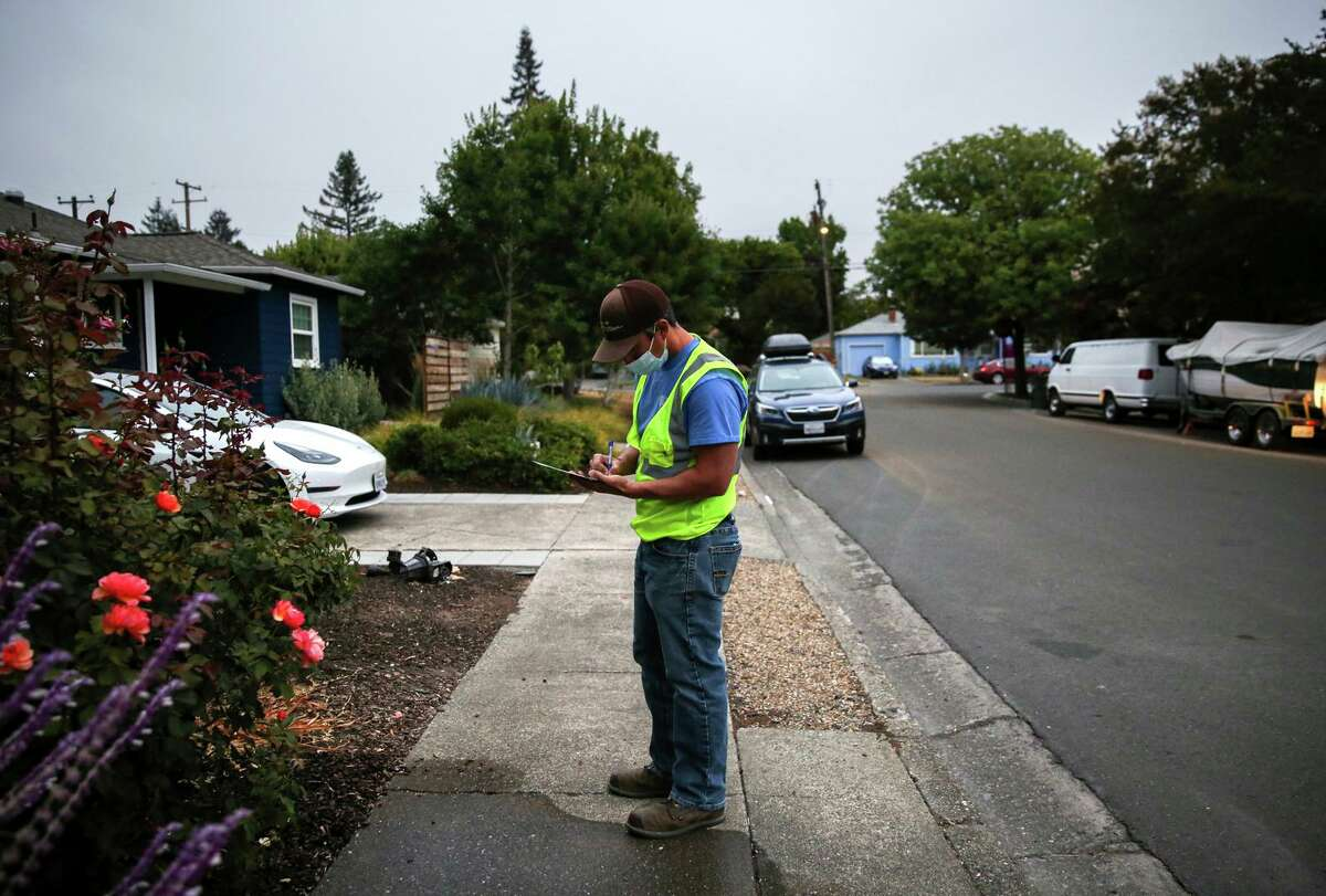 Utility system operator Shiloh Jones writes a notice to a resident not adhering to water restrictions in Santa Rosa. Jones patrols neighborhoods giving notice to residents about city water restrictions.