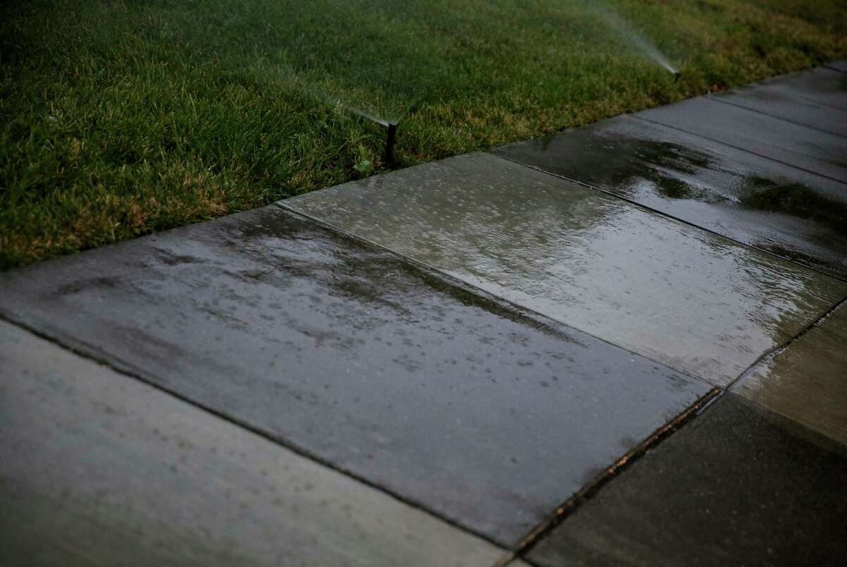 Sprinklers drench the sidewalk in front of a residence in Santa Rosa on Wednesday. The city has created a waste water patrol where employees drive through neighborhoods giving notice to residents who are not adhering to water cutbacks.