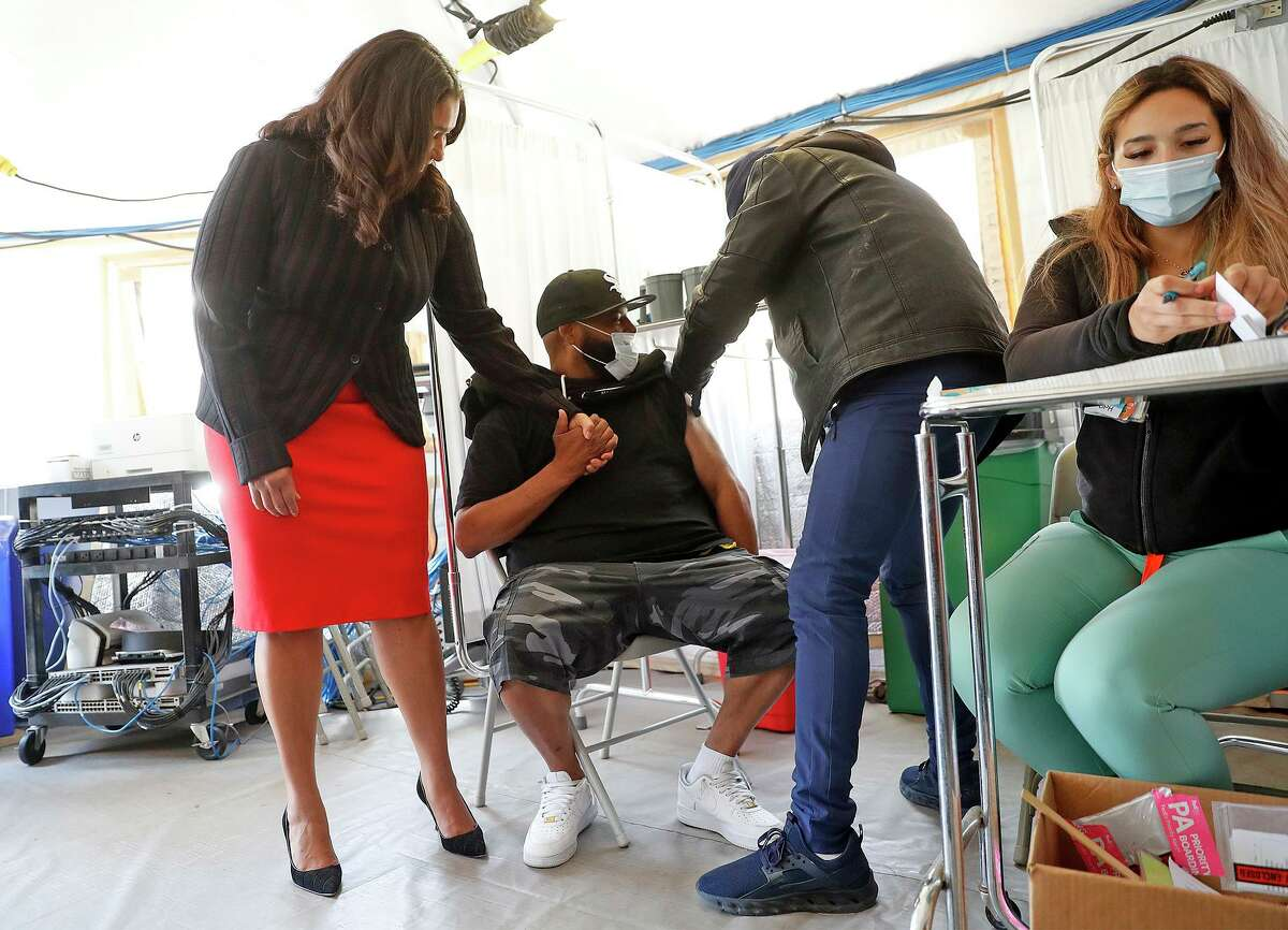 S.F. Mayor London Breed holds the hand of Jamal Gregory as he gets vaccinated at Southeast Health Center in the Bayview.
