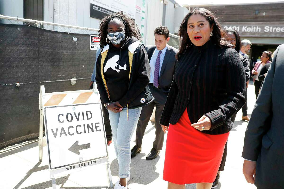 San Francisco Mayor London Breed leads Tianna Hicks, mother of NFL rookie Najee Harris, to get a COVID vaccination at Southeast Health Center in the Bayview neighborhood of San Francisco.