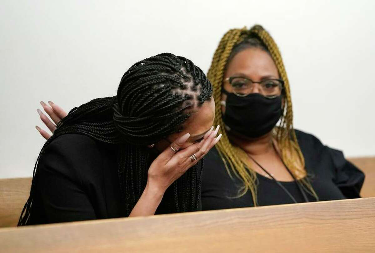 Ashley Moss (left), wife of Richard Sherman, is comforted during a court hearing at King County District Court.
