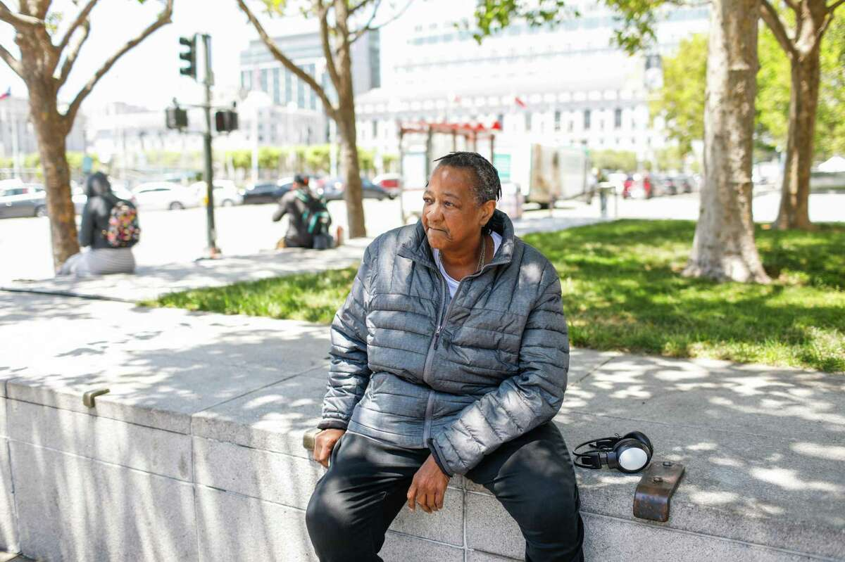 Pamela Tisdale waits for the bus as she runs errands in San Francisco. Tisdale lives in a hotel that has been temporarily leased by the city for homeless people during the pandemic. She said she has to deal with rats on a daily basis, and also had to recently vacate her room when a pipe burst.
