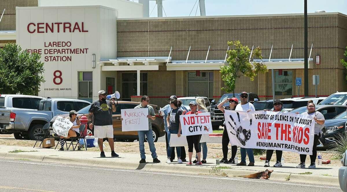"""Manifestantes muestran su oposición a la """"ciudad de tiendas"""" en Laredo, el jueves 15 de julio de 2021, en el exterior del Centro de Administración del Departamento de Bomberos de la Ciudad de Laredo donde líderes locales hablaron de la afluencia de casos de COVID en los inmigrantes que buscan asilo. ."""