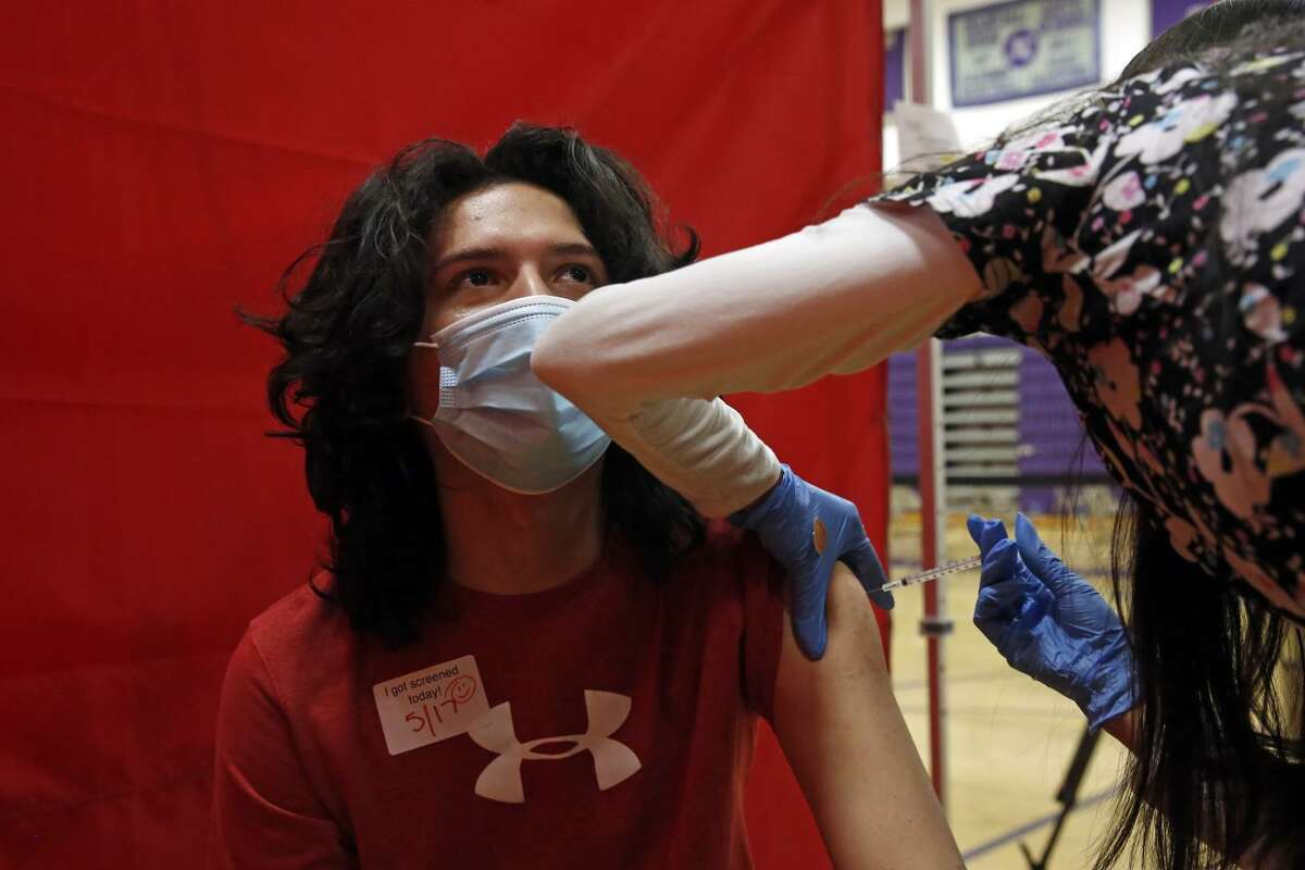 Aragon Leep, 17, is vaccinated with Pfizer at the Manual Arts High School basketball and gym building in downtown on Monday, May 17, 2021 in Los Angeles, CA. The school is one of 200 sites that the Los Angeles Unified School District has deployed mobile vaccination teams to get as many shots into students' arms as possible. (Dania Maxwell / Los Angeles Times/TNS)