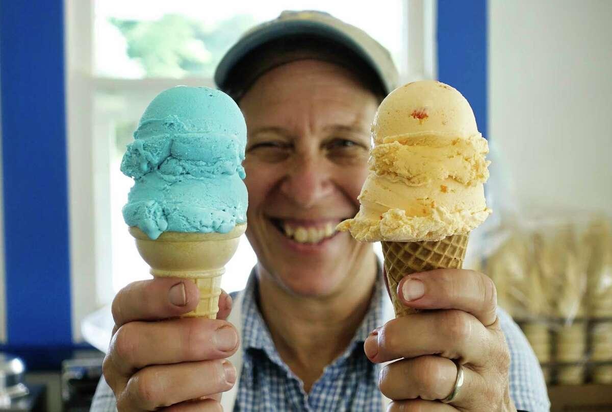 Pamela Allie-Morrill, owner of Moxie's Ice Cream in Wynantskill, holds a cone of blue moon ice cream, left, and orange-pineapple ice cream.(Paul Buckowski/Times Union)