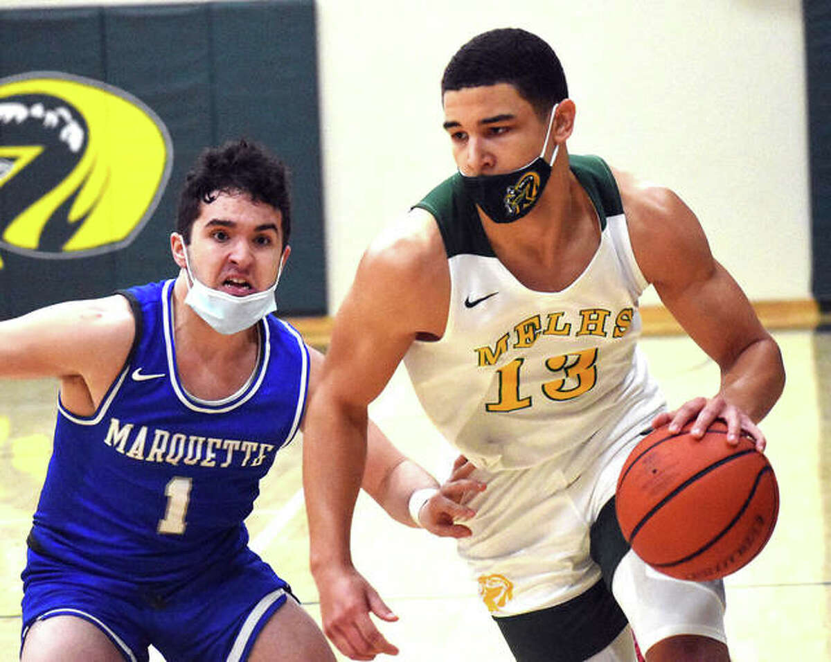 Metro-East Lutheran senior A.J. Smith (right) drives past Marquette Catholic's Parker Macias during a game last season at Hooks Gym in Edwardsville. Smith is the 2021 Telegraph Small-Schools Boys Basketball Player of the Year.
