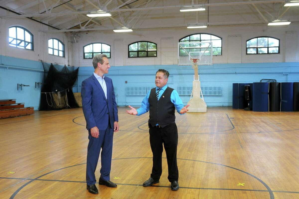 Pat Charmel, left, President and CEO of Griffin Hospital, speaks with Ansonia Mayor David Cassetti in the gymnasium of the Ansonia Armory, in Ansonia, Conn. July 14, 2021.