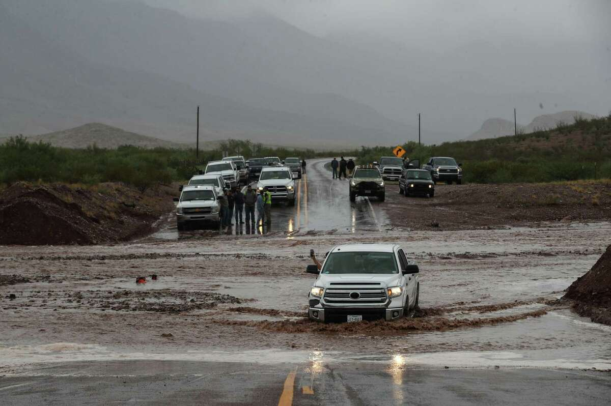 """A truck crosses a flooded area known locally as """"the dip,"""" Monday, June 28, 2021, near Van Horn. A group of people, including Blue Origin employees and contractors, waited to cross the flooded road after heavy rains moved through the area."""