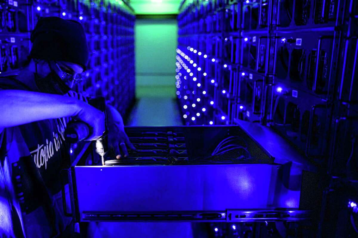 An engineer uses a drill to carry out maintanence to a mining rig draw housing graphics processing units (GPU) at the Evobits crypto farm in Cluj-Napoca, Romania, on Jan. 22, 2021.