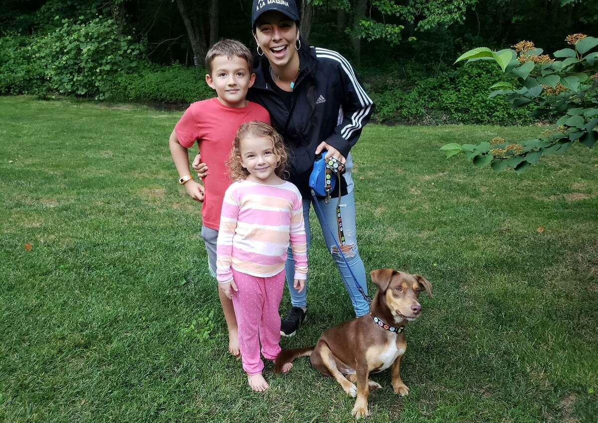 Kimberly Quiros of Old Lyme, right, is shown with her children, 7-year-old RJ, left; and 4-year-old Izzy, right; as well as their new dog, Milo.