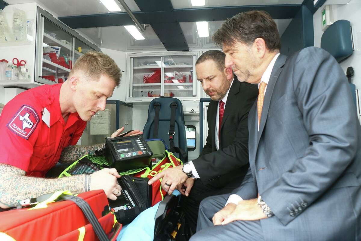 CCEMS Paramedic Joseph Wells demonstrates critical care equipment to American Jet International CEO Roger Woolsey in the bay of the ambulance while CCEMS CEO Wren Nealy, Jr. looks on. The two organizations signed a contract to work together for critical care medical transport services and organ procurement operations across the country and around the globe.