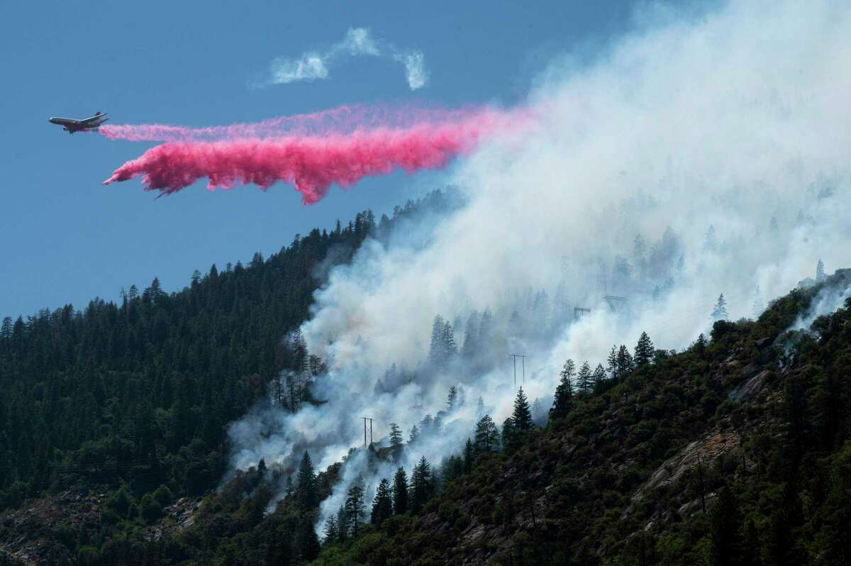 Air tanker drops fire retardant to battle the Dixie Fire in the Feather River Canyon in Plumas County, Calif. The fire grew to just under 8,000 acres and was 7% contained.