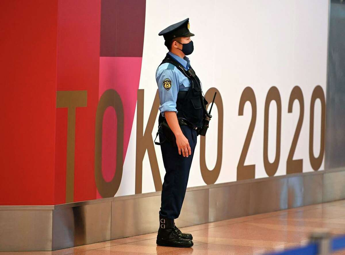 A police officer stands guard for the upcoming Tokyo 2020 Olympic Games at the arrival floor at Tokyo international airport in Tokyo on July 15, 2021.