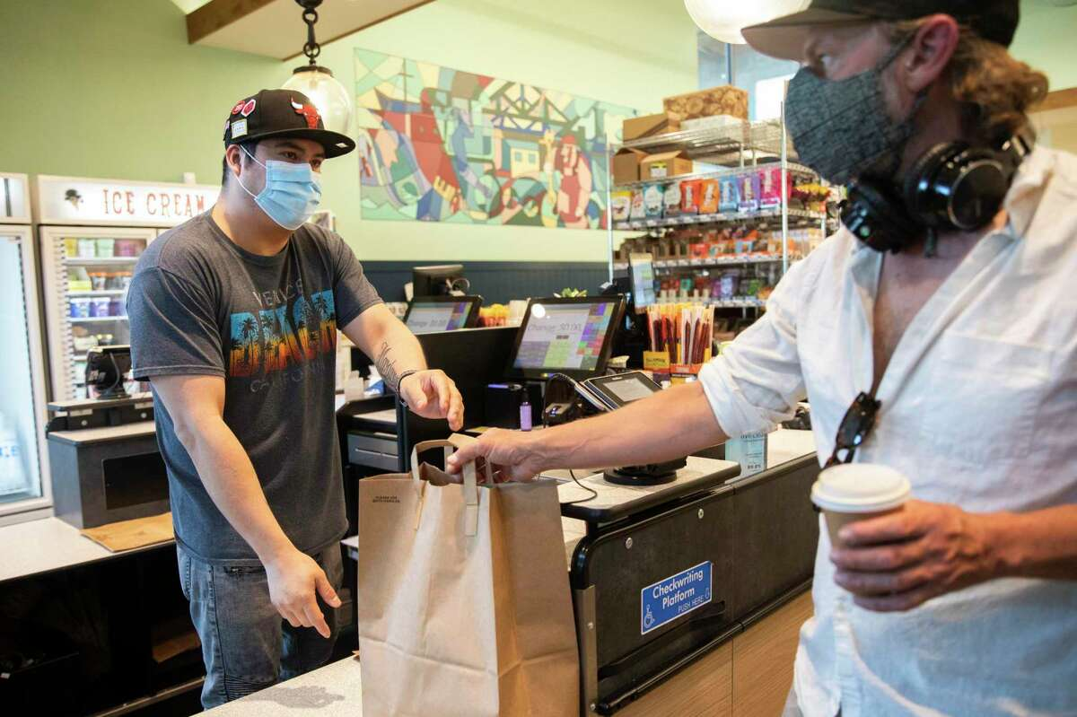A cashier helps a man check out while shopping at Rocky's Market in Oakland in June. Alameda County currently does not require vaccinated people to wear masks in most indoor settings - though many still do - but it is considering changes to its recommendations as the contagious delta variant spreads.