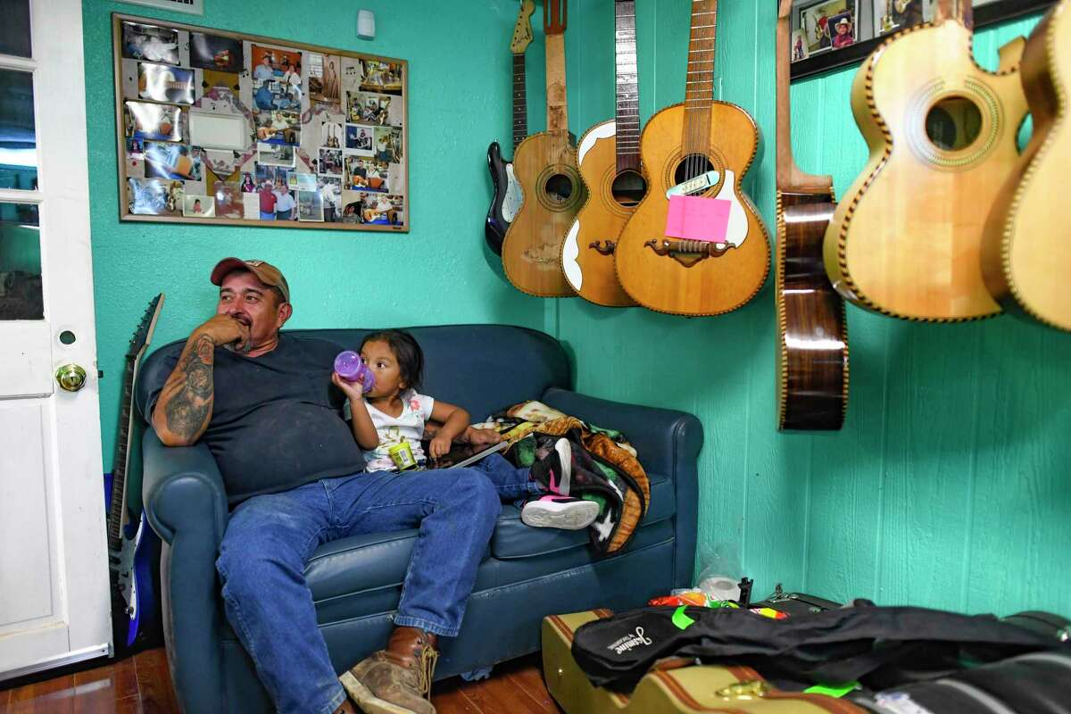 George Macias relaxes with his girlfriend's child, Aliyah, in his workshop on San Antonio's southwest side. Many say the Macias family's instruments are the finest in the world. The 12-string bajo sexto is integral to conjunto music.