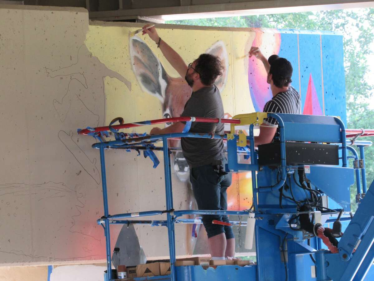 Cam DeCaussin and Joey Salamonwork on the second half of a mural beneath the M20 Traffic Bridge Thursday, July 15.